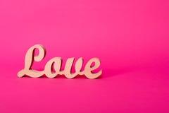 Formułuje miłości, drewniani listy na menchiach tapetuje z przestrzenią dla teksta Walentynki ` s dnia tło Lovestory lub ślubny w Obrazy Royalty Free