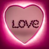 Formułuje miłości kłaść out z sztucznymi kwiatami wśrodku czerwonego serca obraz stock