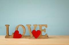 Formułuje miłości od drewnianych listów i czerwonych serc Obrazy Stock