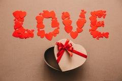 Formułuje miłości od serc i otwiera prezenta pudełko w formie serca Obraz Stock