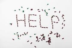 Słowo pomoc tworząca pigułkami Fotografia Royalty Free