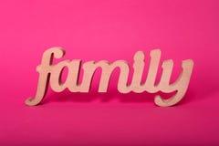 Formułuje rodziny, drewniani listy na menchia papieru tle Miłości i jedności pojęcie obraz stock