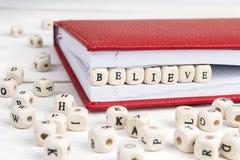 Formułuje Wierzę pisać w drewnianych blokach na białym woode w notatniku Fotografia Royalty Free