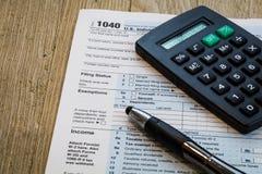 Formulário da preparação do imposto com pena e calculadora Fotos de Stock Royalty Free