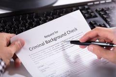 Formulário de candidatura da verificação de Person Hand Filling Criminal Background fotos de stock