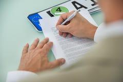 Formulário de enchimento do contrato de venda do carro do homem de negócios foto de stock