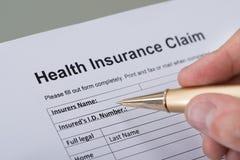 Formulário de enchimento do seguro de saúde da mão Fotografia de Stock Royalty Free