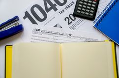 Formulário de imposto 1040, cadernos, grampeador e calculadora foto de stock
