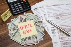 Formulário de imposto com nota pegajosa do 15 de abril, de dólar americano e da calculadora Imagem de Stock Royalty Free