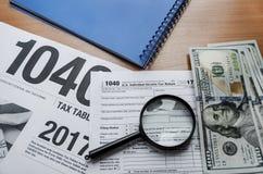 Formulário de imposto 1040, dólares, lente de aumento e bloco de notas em uma tabela de madeira imagem de stock royalty free