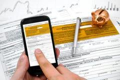 Formulário de imposto da renda do polimento do enchimento do homem no móbil Fotografia de Stock