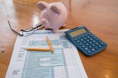 Formulário de imposto do IRS com mealheiro e o lápis quebrado calculadora fotografia de stock royalty free