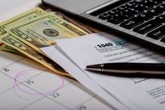 Formulário de imposto 1040 dos EUA IRS e um calendário Veiw superior dos dólares de U S, foco macio seletivo imagens de stock