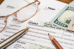formulário de imposto 1040EZ pelo ano 2016 com pena e vidros Imagens de Stock Royalty Free