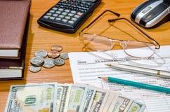 Formulário de imposto 1040 para 2016 com pena, vidros, dólares Fotografia de Stock Royalty Free