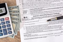Formulário de imposto W4 com dinheiro e pena fotos de stock