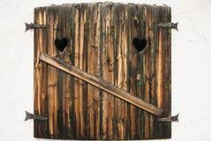 Formulário de madeira do coração das janelas Brown na parede branca imagens de stock