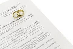 Formulário do divórcio com duas alianças de casamento Fotos de Stock Royalty Free