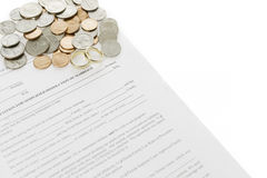 Formulário do divórcio com a pilha das moedas e das alianças de casamento dos pares Fotografia de Stock