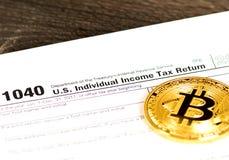 Formulário individual da declaração de rendimentos 1040 da renda com a moeda metálica do bitcoin foto de stock royalty free