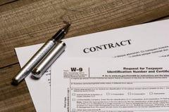 Formulário W-9 do IRS e um contrato fotografia de stock