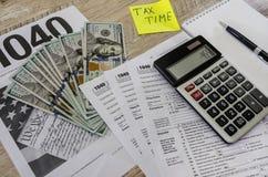 Formulários de imposto 1040, bloco de notas, pena, dólares e uma calculadora em uma tabela de madeira imagem de stock