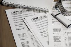 Formulários de imposto caderno 1040, relógio de pulso e vara instantânea na tabela imagens de stock