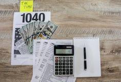 Formulários de imposto 1040, calculadora, dólares, bloco de notas e pena em um fundo de madeira fotos de stock