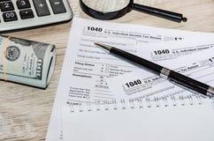 Formulários de imposto 1040, dólares americanos, pena e calculadora no fundo de madeira foto de stock