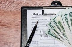 Formulários de imposto 1040, dólares americanos, pena no fundo de madeira imagens de stock