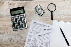 Formulários de imposto 1040, dólares, calculadora, pena e lente de aumento na tabela cinzenta, de madeira fotos de stock
