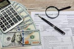 Formulários de imposto 1040, dólares, calculadora, pena e lente de aumento na tabela cinzenta, de madeira fotografia de stock
