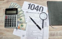 Formulários de imposto 1040, dólares, calculadora, pena e lente de aumento na tabela cinzenta, de madeira imagem de stock