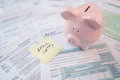 Formulários de imposto do IRS com mealheiro e lembrete Foto de Stock Royalty Free