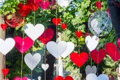 Formulários dos corações vermelhos e brancos que penduram em árvores Imagens de Stock Royalty Free