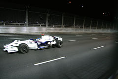 Formula 1 car speeding at the night race. Royalty Free Stock Image