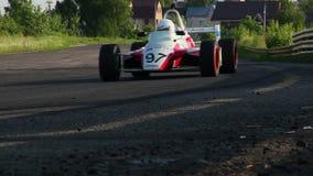 Formula 1 car driving desert circuit, taking fast turn