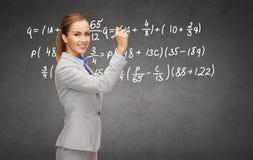 Formula di scrittura della donna di affari con l'indicatore Immagini Stock