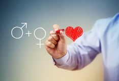The formula for love. A man drawing male and female gender symbols and a red heart Stock Images