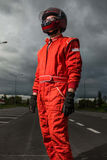 Formula one driver. Posing in dramatic sky background, outdoor, wearing protective helmet and red racing suit royalty free stock photos