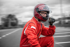Formula one pilot. Formula one driver posing in dramatic sky background, outdoor, wearing protective helmet and red racing suit stock photos
