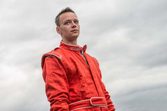 Formula one pilot. Formula 1 pilot in red racing protective suit. Outdoor. Sky background.Series Royalty Free Stock Image