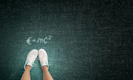 Formula in physics. Top view of girl in sport shoes standing on blackboard Stock Photography