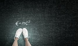 Formula in physics. Top view of girl in sport shoes standing on blackboard Royalty Free Stock Image