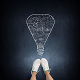 Formula in physics. Top view of girl in sport shoes standing on blackboard Stock Photos