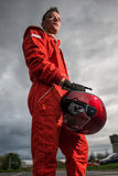 Formula 1 pilot. In red racing protective suit and helmet in his hand. Outdoor stock photography