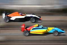 Formula 4.0 race cars racing at high speed. On speed track with motion blur at sunny day royalty free stock photos