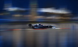 Formula 2.0 races down the streets. Formula 2.0 race car racing at high speed with motion blur in front of city background Stock Images