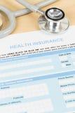 Formulaire de demande d'assurance médicale maladie avec le stéthoscope Images stock