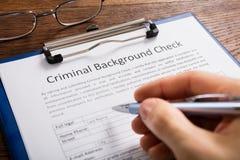 Formulaire de demande de Person Filling Criminal Background Check image stock